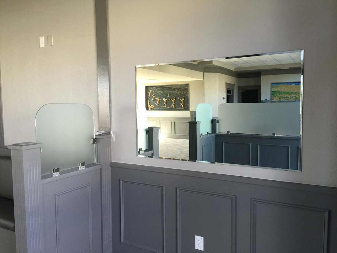 glass partition on top of pony wall to separate dining areas