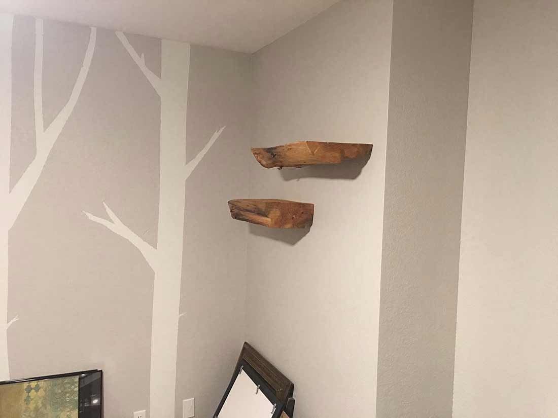 Small wood shelves and stenciled trees on grey walls