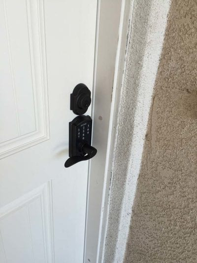 Newly installed door lock with number pad on white door