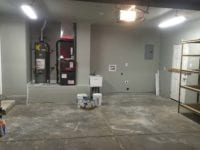 Garage during remodel, with water heater and old shelving