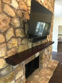 Fireplace with new stone construction on wall with mounted TV
