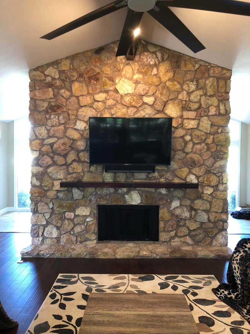 Fireplace remodel with stone wall and TV above fireplace