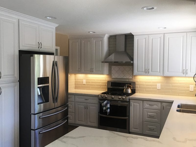 A kitchen remodel with classic eggshell cabinetry and stainless appliances