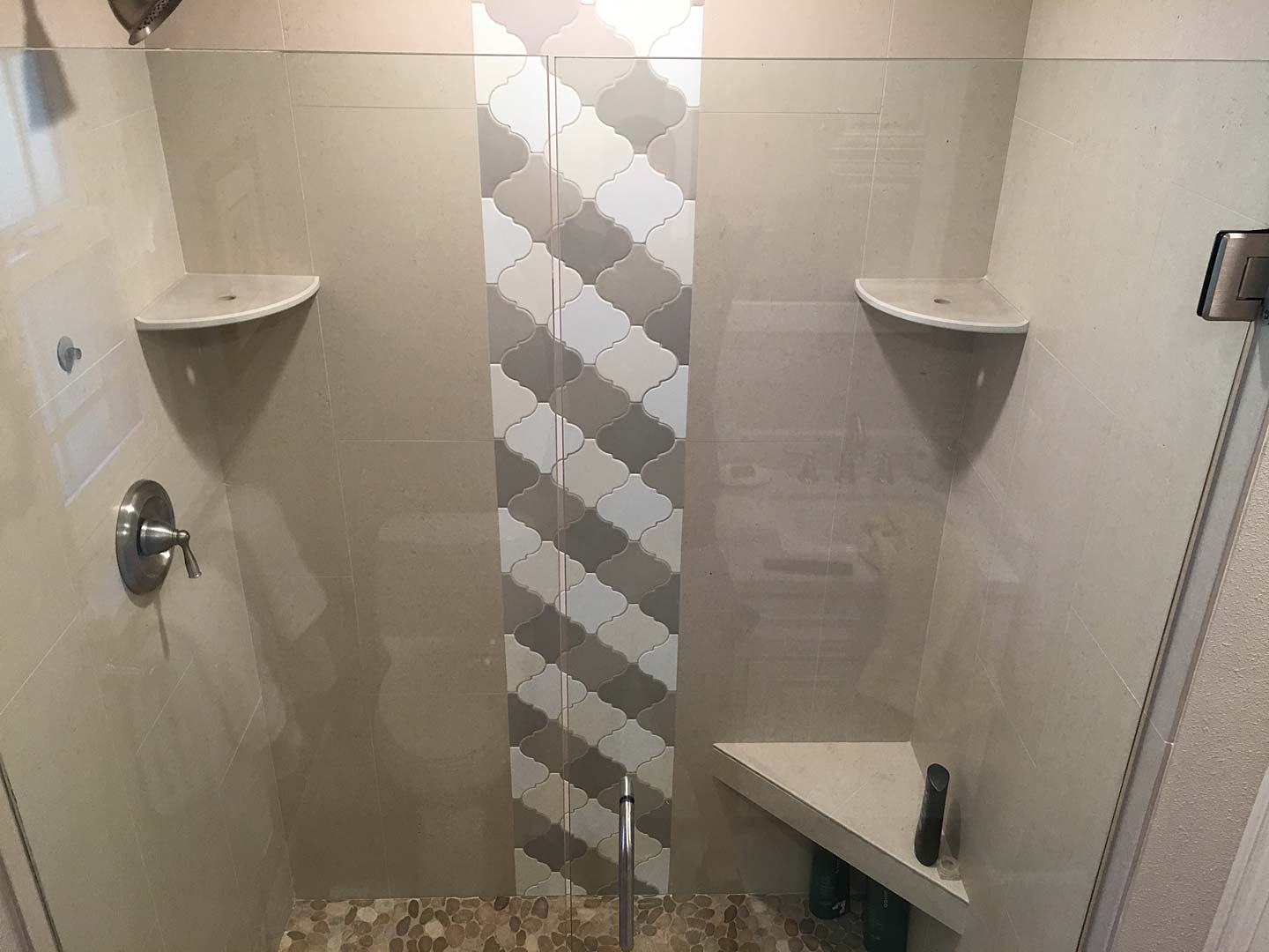 Beautiful shower remodel with glass door and unique tiling pattern