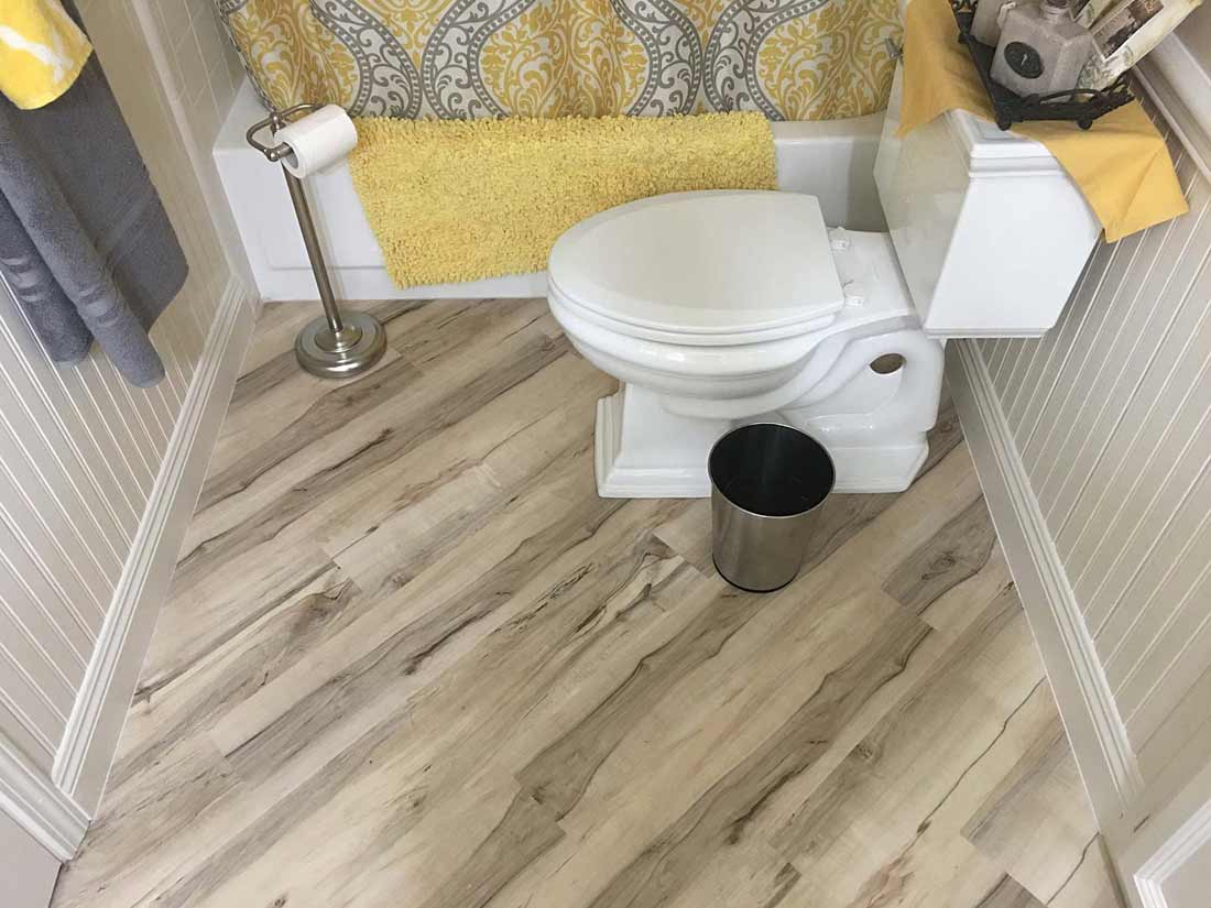 New toilet, bathtub, and flooring with yellow and grey decor