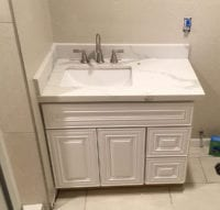 white bathroom sink and cabinet installed