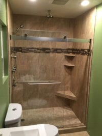 neutral shower remodel and tile work with green walls