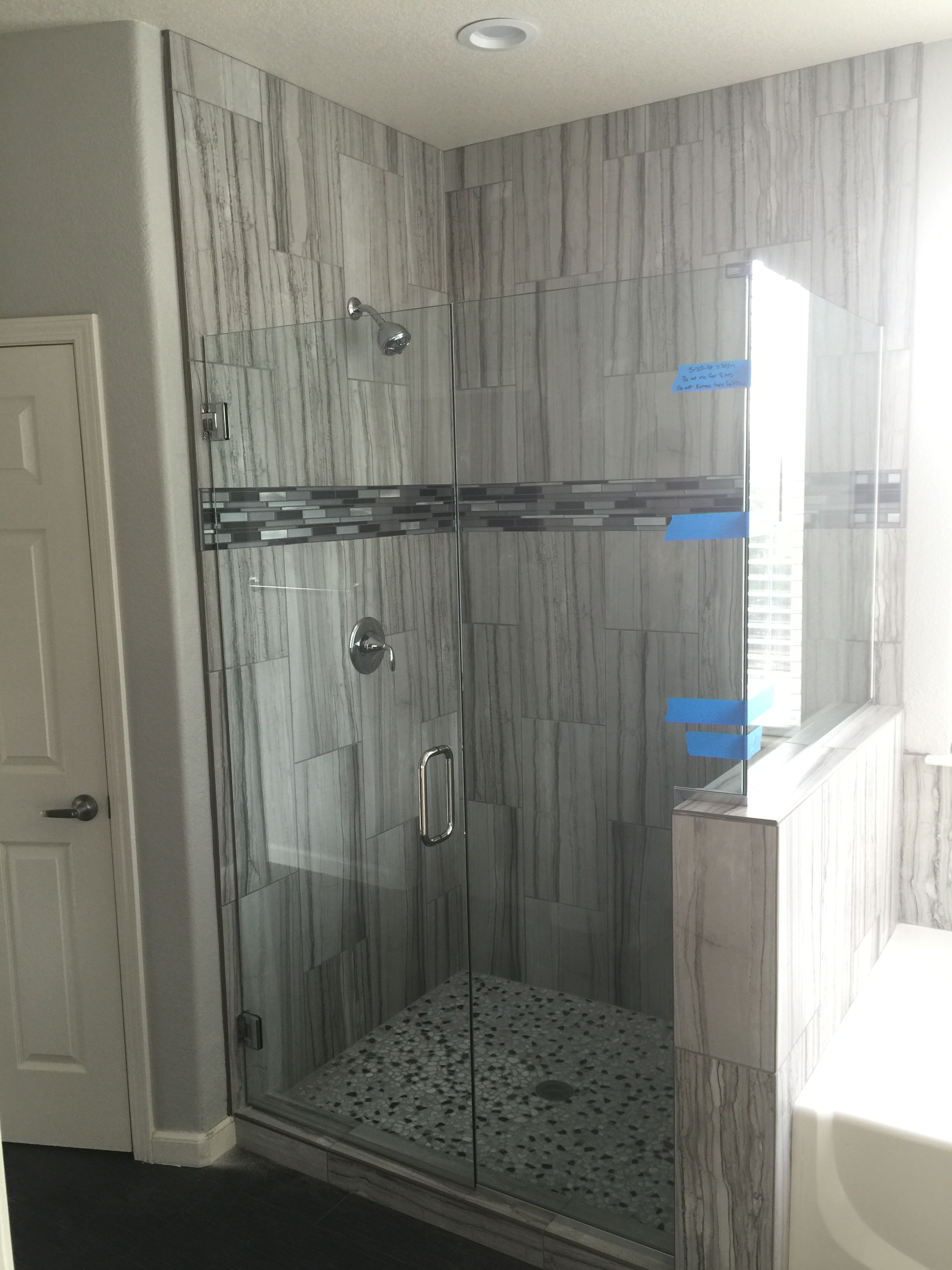 standalone shower installation with glass enclosure