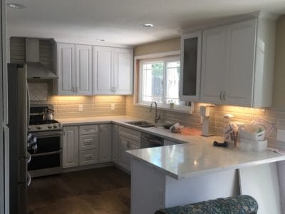 kitchen remodel with white cabinets and tile backsplash