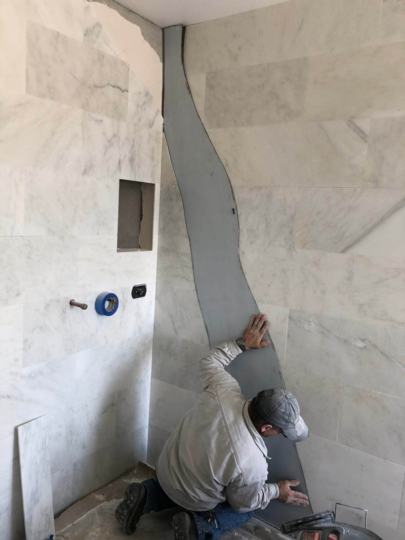 contractor placing stainless steel inlay during shower remodel in Manteca