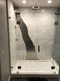 Frameless double glass door shower with stainless steel inlaid into the white carrara marble tile